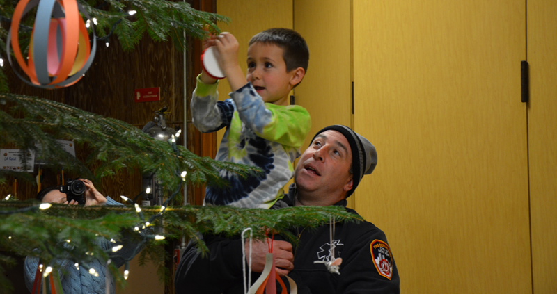 Young boy decorating christmas tree with help from fireman